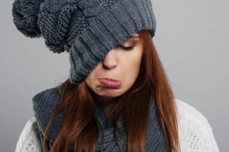 jeune femme habillé chaudement pour l'hiver et un peu triste